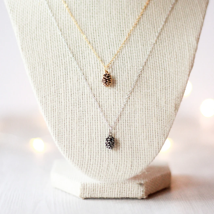 Tiny pine cone necklace by Birch Jewellery in silver and gold, styled on a jewellery display
