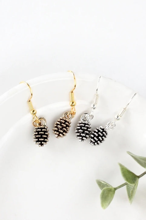 Pine cone earrings by Birch Jewellery; silver and gold; styled on a white ceramic dish