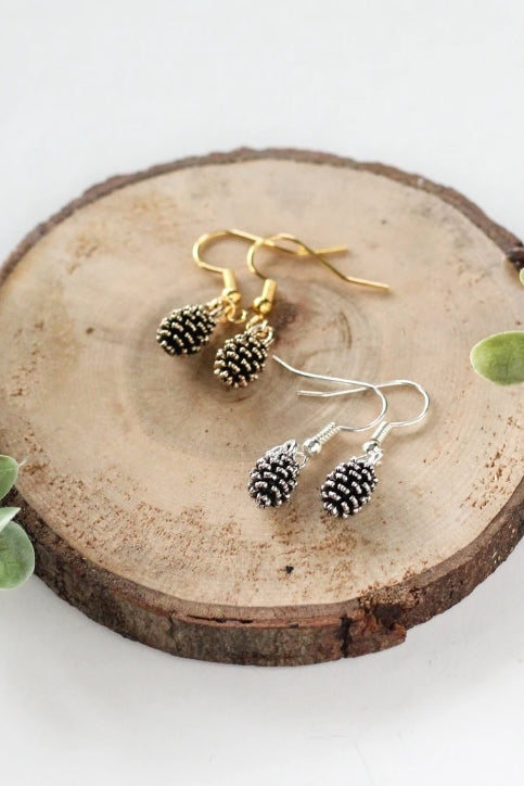 Pine cone earrings by Birch Jewellery; silver and gold, styled on a stump of wood
