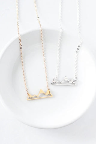 Mountain necklace by Birch Jewellery; silver and gold; flat lay styled on a white ceramic dish