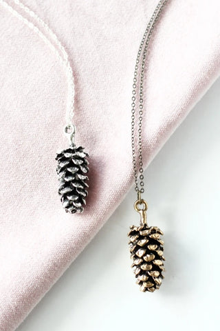 Large pine cone necklace by Birch Jewellery; flat lay; in silver and gold