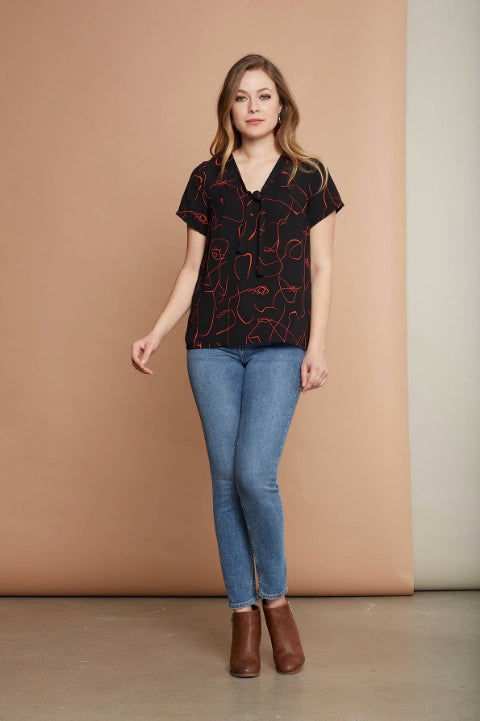 Angie blouse by Cherry Bobin in Abstract Faces; black top with abstract face linework; styled with blue jeans and a cognac leather heeled boot
