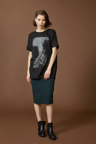 Wild tunic by Cokluch; black speckled material; grey silkscreened wolf graphic; drop-shoulder; rounded neckline; full-length front view; styled with an emerald skirt and chunky black ankle boots