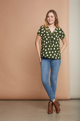Angie blouse by Cherry Bobin in green with white polka dots; styled with medium wash blue jeans and a cognac brown leather heeled boot