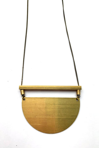 Guppe long necklace by Darlings of Denmark; solid horizontal bar and brass plate semi-circle pendant; raw brass; flat lay