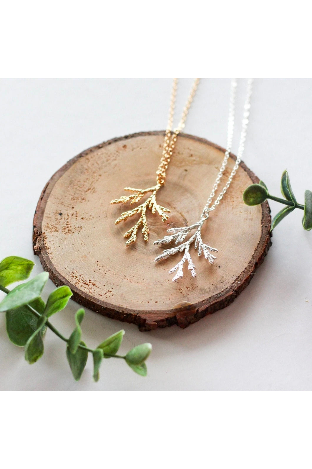 Juniper branch necklace by Birch Jewellery; shown in silver and hold; flat lay on a stump of would and with eucalyptus branches