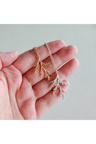 Juniper branch necklace by Birch Jewellery; shown held in a hand, in silver and gold