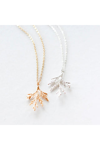 Juniper branch necklace by Birch Jewellery; shown in silver and hold; flat lay on a white surface
