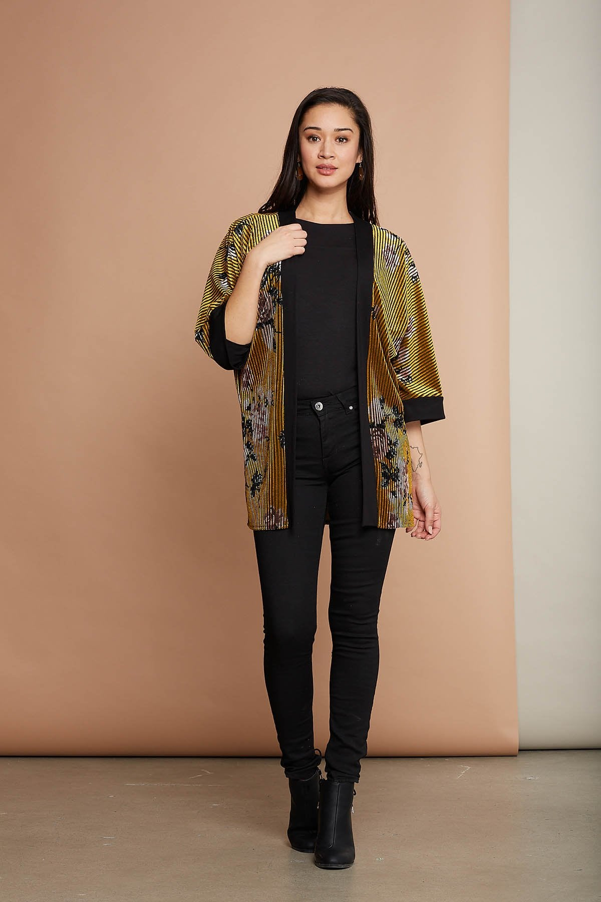 Sora cardigan by Cherry Bobin; yellow ribbed texture velvet, contrast black cuffs at the sleeves, lilac floral pattern; kimono style cardigan; styled over a black tank top, black skinny jeans, and black boots