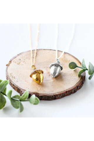 Large acorn necklace by Birch Jewellery; shown in silver and gold; flat lay; styling on a stump of wood and with eucalyptus branches