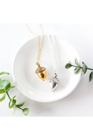 Large acorn necklace by Birch Jewellery; shown in silver and gold; flat lay; styling on a white ceramic dish and with eucalyptus branches