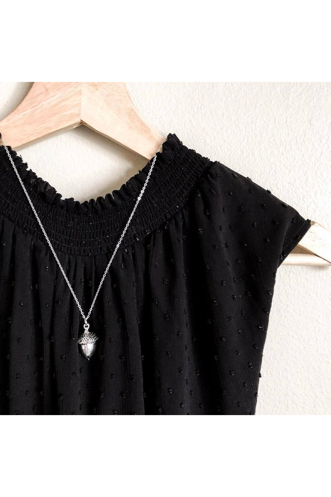 Large acorn necklace by Birch Jewellery; shown in silver; flat lay; styled on a black top on a wooden hanger