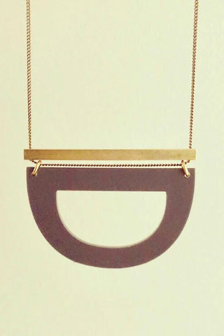 Luppe long necklace by Darlings of Denmark; solid brass horizontal bar and acrylic hollowed out half circle; hanging flat lay