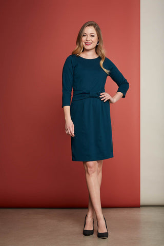 Eleanor dress by Cherry Bobin in turquoise; rounded neckline, 3/4-length sleeves, straight cut skirt, hits above the knee, belted detail pulls in the waist; styled with black high heels