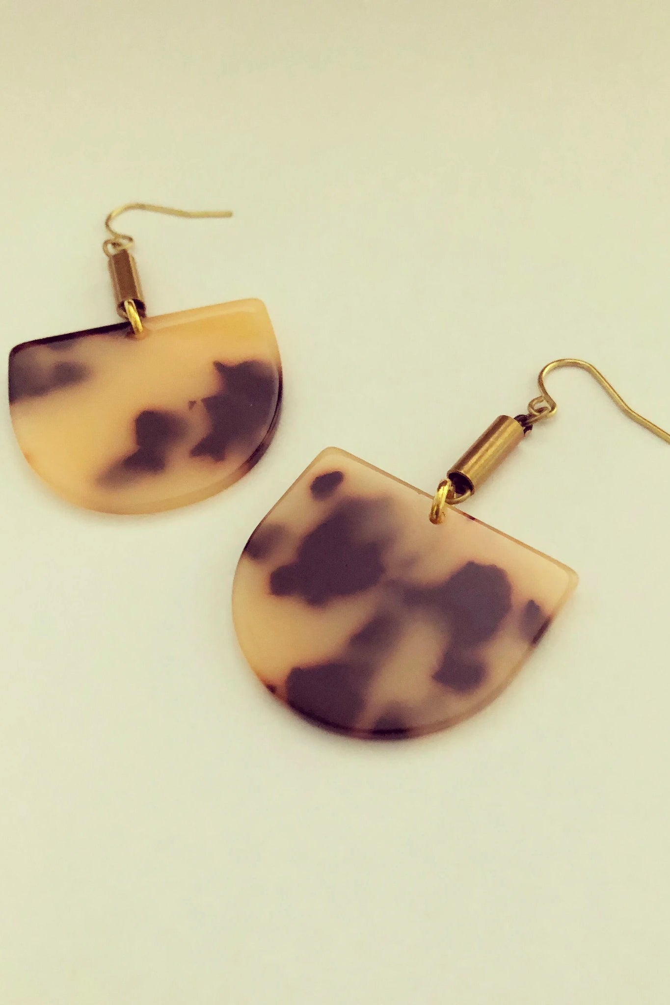 Ruve earrings by Darlings of Denmark; Acrylic, tortoise shell, semi-circle dangle earrings with short brass tube; raw brass and acrylic; flat lay