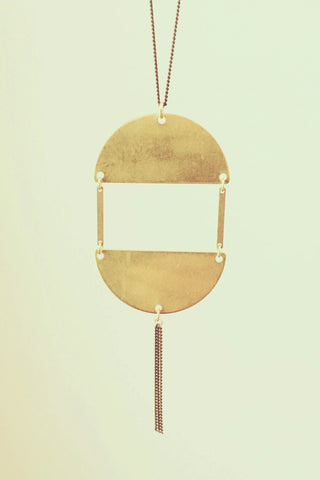 Shullie long necklace by Darlings of Denmark; raw brass; two semi-circles attached by two slim sticks; dangle chain detail; flat lay