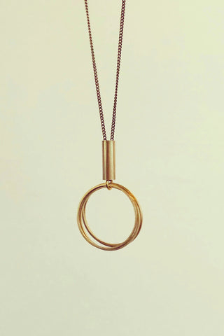 Taliah long necklace by Darlings of Denmark; raw brass; four mini thin hoops hanging off a short tube; flat lay
