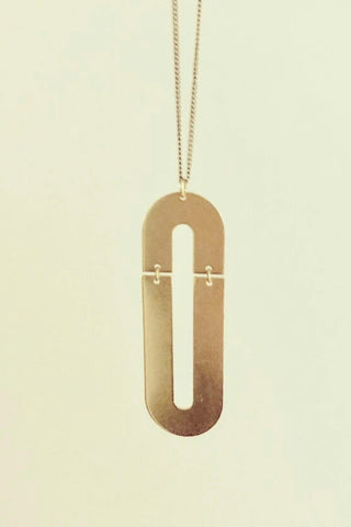 Trub long necklace by Darlings of Denmark; raw brass; double arch design; flat lay