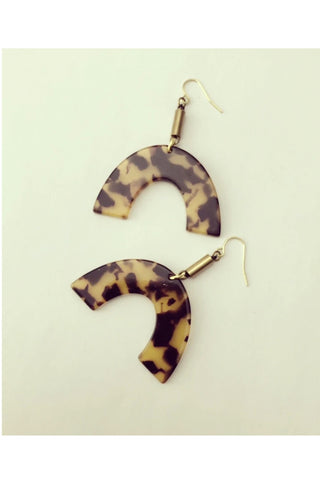Vuttue dangle earring by Darlings of Denmark; tortoise shell acrylic arch hanging off raw brass tubes; flat lay