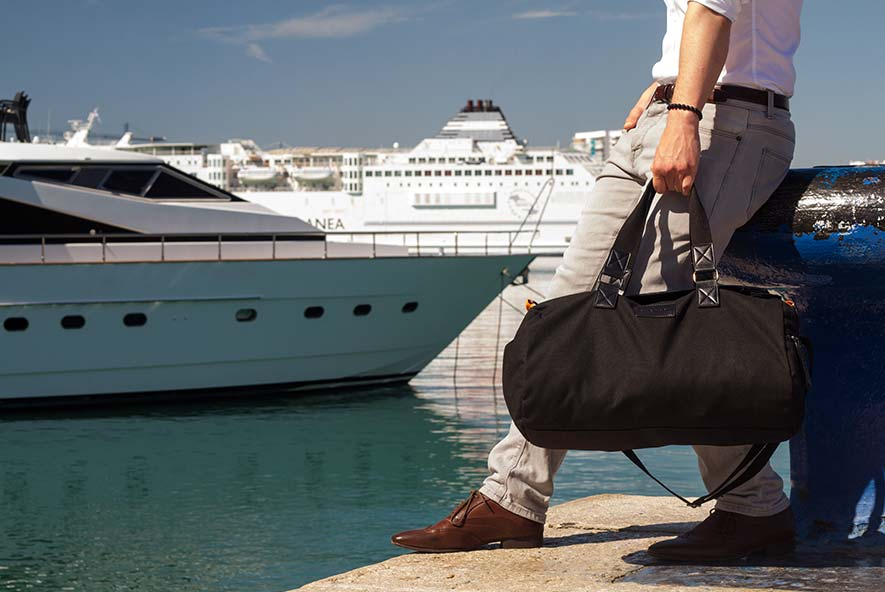 Vanacci Duffel bag  in black canvas at the harbor ready for a luxury boat trip.