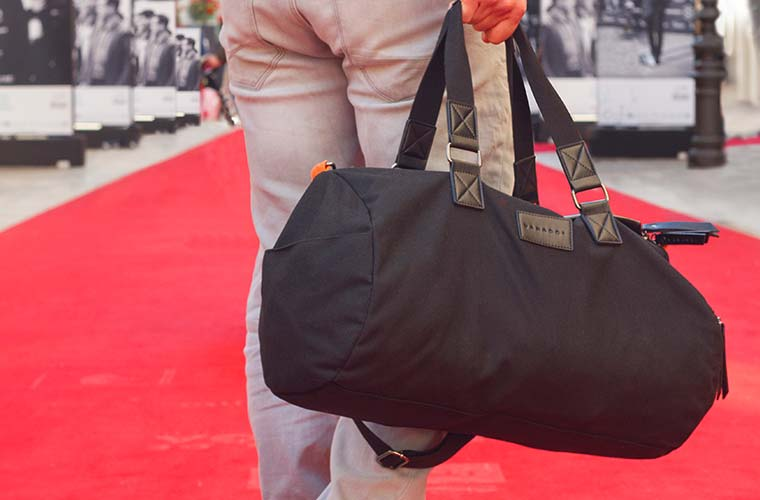 Vanacci Roma Duffel Bag Held By Man On Red Carpet, Walking Away