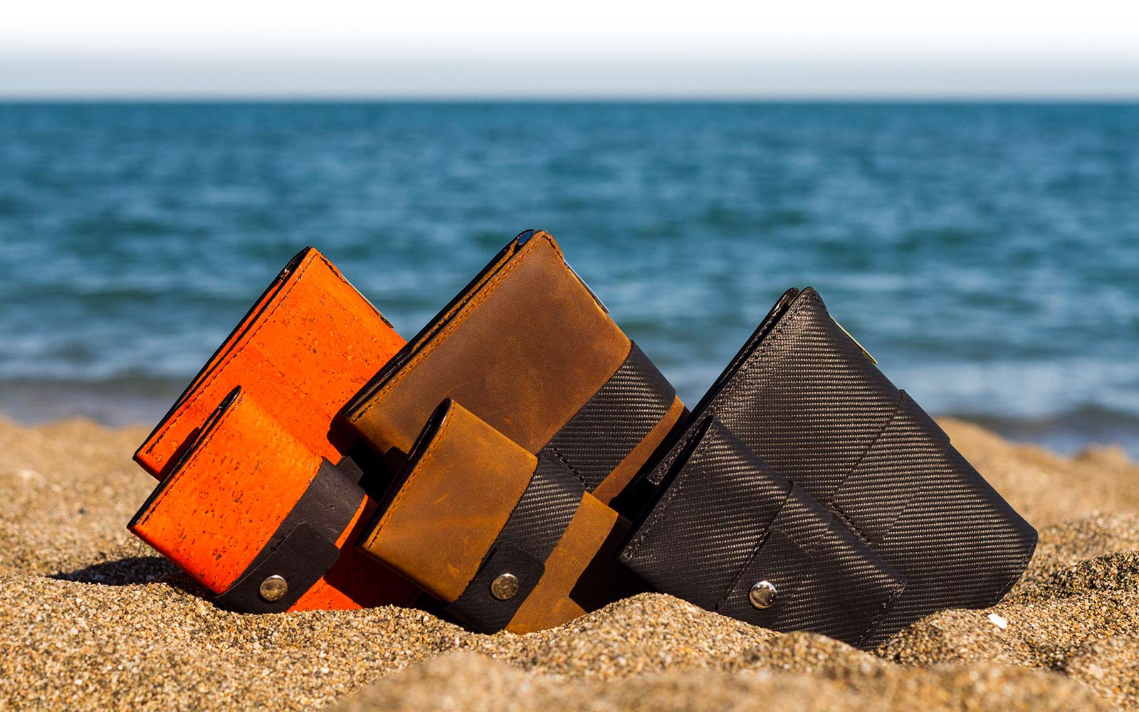 Traveller and Tasca wallets, black, brown and orange, on beach