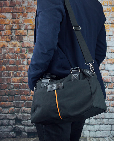 Vanacci canvas messenger bag in black worn by a man
