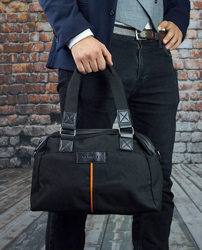 Vanacci canvas messenger bag in black held by a man