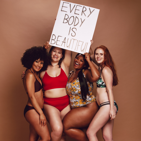 """4 women with different body types holding a sign that says """"Every body is beautiful""""."""