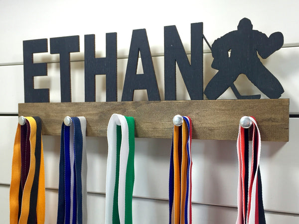 Our personalized hockey goalie medal holder is a unique gift for the goalie in your life. This display will be the perfect way for them to show off all of their well-deserved awards. This design comes in a variety of colors, or you can pick from our other choices of sports or phrases so we can customize it just the way you want!