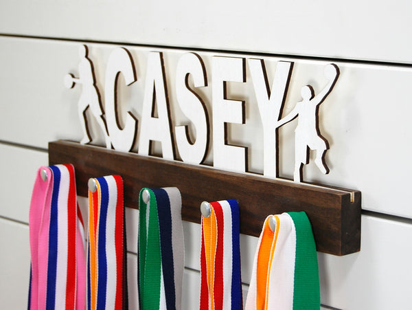Our personalized basketball medal holder is a unique gift for the b-baller in your life. This display will be the perfect way for him to show off all of his awards. This design comes in a variety of colors, or you can pick from our other choices of sports or phrases so we can customize it just the way you want!
