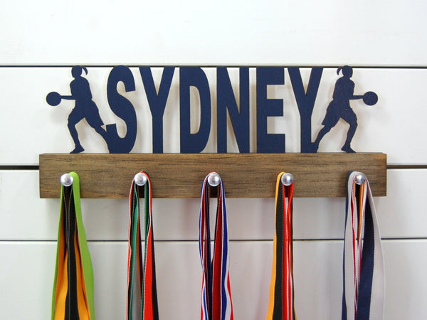 Our personalized basketball medal holder is a unique gift for the b-baller in your life. This display will be the perfect way for her to show off all of her awards. This design comes in a variety of colors, or you can pick from our other choices of sports or phrases so we can customize it just the way you want!