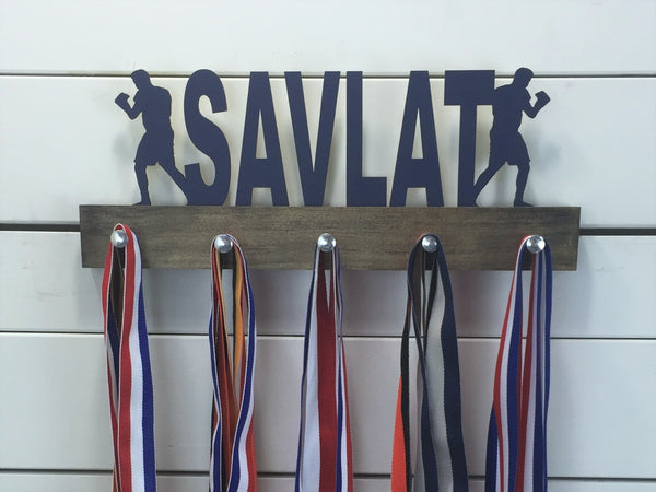 Our personalized boxing medal holder is a unique gift for the boxer in your life. This display will be the perfect way for them to show off all of their awards. This design comes in a variety of colors, or you can pick from our other choices of sports or phrases so we can customize it just the way you want!