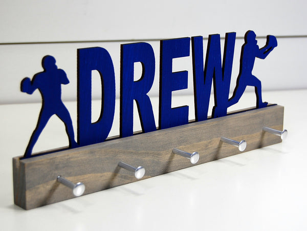Our personalized football medal holder is a unique gift for the football player in your life. This display will be the perfect way for him to show off all of his well-deserved awards. This design comes in a variety of colors, or you can pick from our other choices of sports or phrases so we can customize it just the way you want!