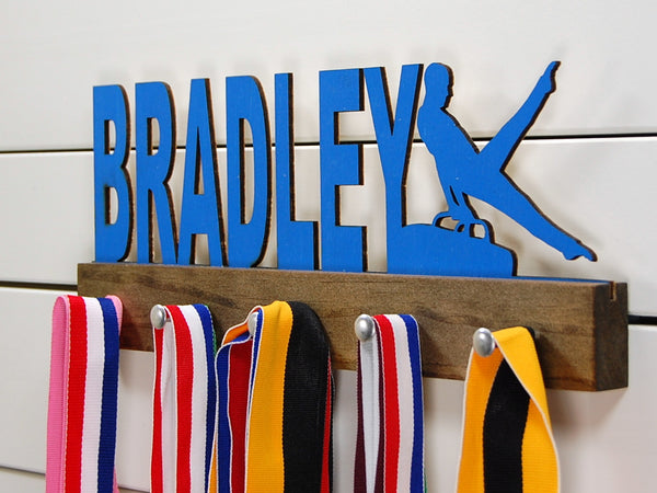 Our personalized gymnastics medal holder is a unique gift for the gymnast in your life. This display will be the perfect way for him to show off all of his well-deserved awards. This design comes in a variety of colors, or you can pick from our other choices of sports or phrases so we can customize it just the way you want!