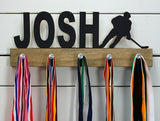 Our personalized hockey medal holder is a unique gift for the hockey player in your life. This display will be the perfect way for them to show off all of their well-deserved awards. This design comes in a variety of colors, or you can pick from our other choices of sports or phrases so we can customize it just the way you want!