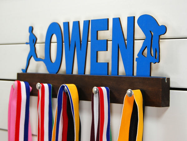 Our personalized multi-sport medal holder is a unique gift for the talented athlete in your life. This display will be the perfect way for them to show off all of their well-deserved awards. This design comes in a variety of colors, or you can pick from our other choices of sports or phrases so we can customize it just the way you want!