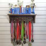 Our personalized trophy shelf and medal holder is a great gift for any winner so they can display all of their awesome awards. This design comes in a variety of colors, or you can pick from our other choices of sports or phrases so we can customize a unique trophy shelf just for you!