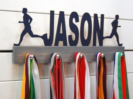 Our personalized running medal holder is a great gift for your runner boy so he can display all of his awesome awards. This design comes in a variety of colors, or you can pick from our other choices of sports or phrases so we can customize it just the way you want!