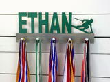 Our personalized skiing medal holder is a unique gift for the skier in your life. This display will be the perfect way for them to show off all of their well-deserved awards. This design comes in a variety of colors, or you can pick from our other choices of sports or phrases so we can customize it just the way you want!