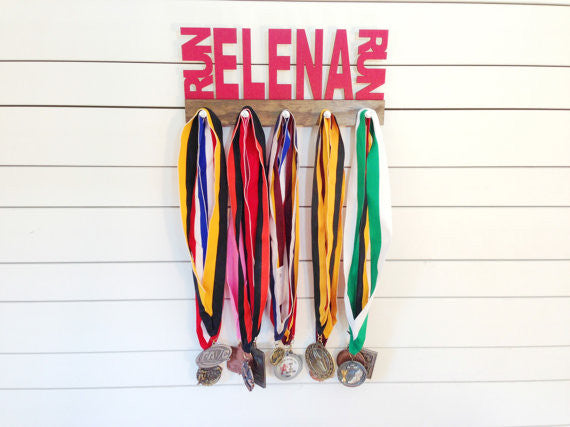 Our personalized running medal holder is a great gift for any runner so they can display all of their awesome awards. This design comes in a variety of colors, or you can pick from our other choices of sports or phrases so we can customize it just the way you want!