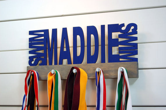 Our personalized swimming medal holder is a great gift for any swimmer so they can display all of their awesome awards. This design comes in a variety of colors, or you can pick from our other choices of sports or phrases so we can customize it just the way you want!