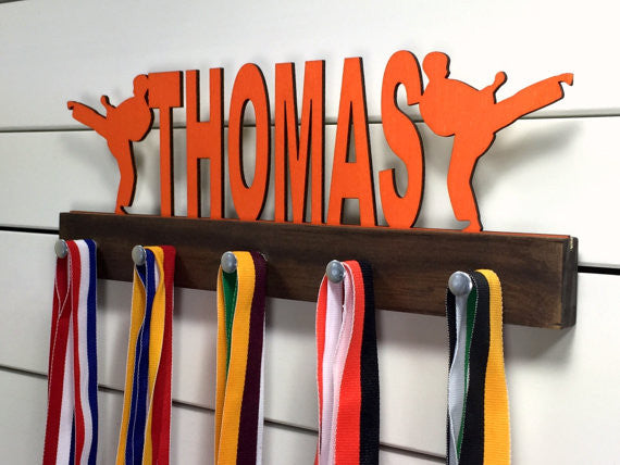 Our personalized martial arts medal holder is a unique gift for the fighter in your life. This display will be the perfect way for them to show off all of their well-deserved awards. This design comes in a variety of colors, or you can pick from our other choices of sports or phrases so we can customize it just the way you want!