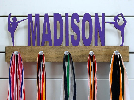 Our personalized dance medal holder is a unique gift for the dancer in your life. This display will be the perfect way for them to show off all of their well-deserved awards. This design comes in a variety of colors, or you can pick from our other choices of sports or phrases so we can customize it just the way you want!