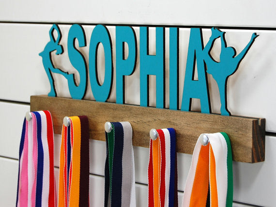 Our personalized figure skater medal holder is a unique gift for the skater in your life. This display will be the perfect way for them to show off all of their well-deserved awards. This design comes in a variety of colors, or you can pick from our other choices of sports or phrases so we can customize it just the way you want!