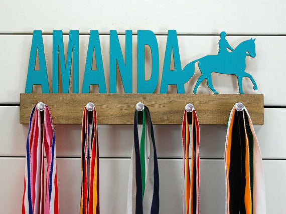 Our personalized equestrian medal holder is a unique gift for the horse-lover in your life. This display will be the perfect way for them to show off all of their well-deserved awards. This design comes in a variety of colors, or you can pick from our other choices of sports or phrases so we can customize it just the way you want!