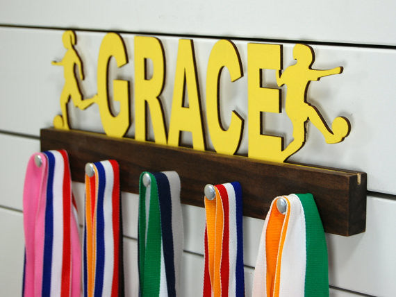 Our personalized soccer medal holder is a unique gift for the soccer player in your life. This display will be the perfect way for her to show off all of her well-deserved awards. This design comes in a variety of colors, or you can pick from our other choices of sports or phrases so we can customize it just the way you want!