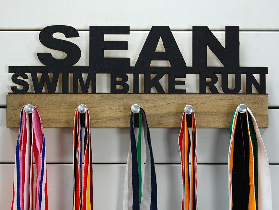 Our personalized triathlon medal holder is a unique gift for any triathlete so they can display all of their awesome and well-deserved awards. This design comes in a variety of colors, or you can pick from our other choices of sports or phrases so we can customize it just the way you want!
