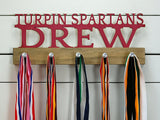 Our medal holder is a unique gift for any athlete with some strong team pride so they can display all of their awesome awards. This design comes in a variety of colors, or you can pick from our other choices of sports or phrases.