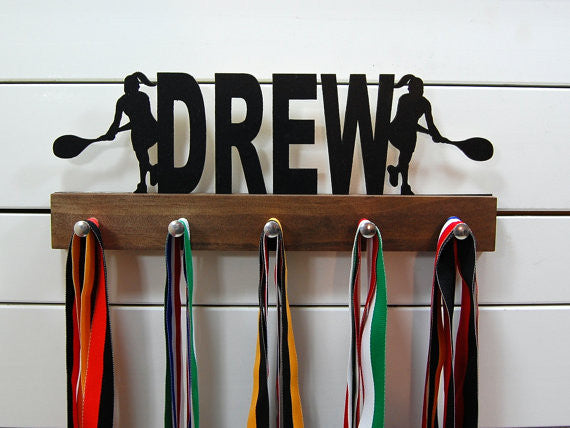 Our personalized tennis medal holder is a unique gift for the tennis player in your life. This display will be the perfect way for her to show off all of her well-deserved awards. This design comes in a variety of colors, or you can pick from our other choices of sports or phrases so we can customize it just the way you want!